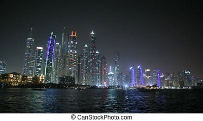 Skyscrapers of Dubai at night and the boat