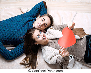 happy couple holding red heart - couple kissing behind paper...