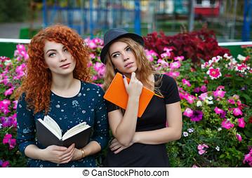 Romantic girlfriend reading a book in park - Best friends in...