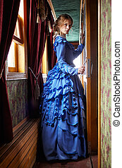 Young woman in blue vintage dress standing in corridor of...