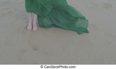 Beauty Girl in green dress stand on sand dune while wind...