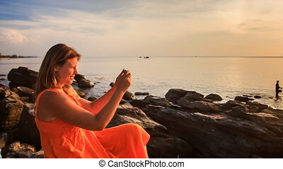 Blond Girl in Red Sits on Sea Stones Uses Iphone at Sunset -...