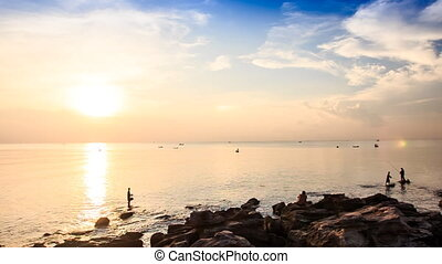 Silhouettes in Sea by Rocks against Sunlight at Sunset -...
