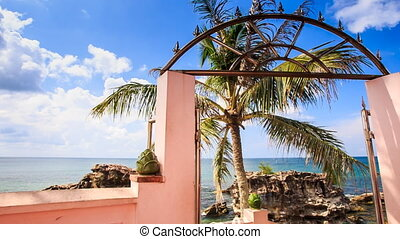 View of Sea Stones Palm through Arch Gate Leading to Beach -...