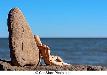 Relaxation at the sea - Wooden dummy sitting on the stony...