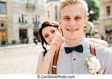 Bride embraces bridegroom - Bride and groom posing at the...