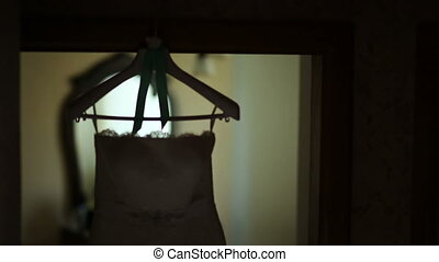 silhouette wedding dress hanging on a hanger in the room