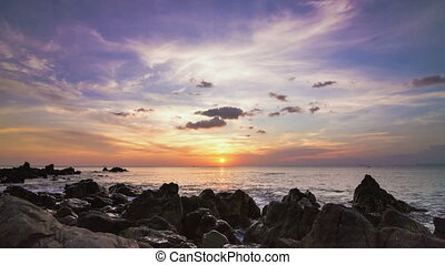 Sea sunset on rock shore pan time lapse