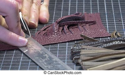 Trunk Maker at work in his workshop - cutting leather...