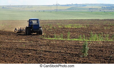 Tractor plowing land - The Tractor Plows the Land