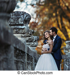 Handsome sensual groom hugging newlywed bride from behind at old castle balcony with autumn trees background