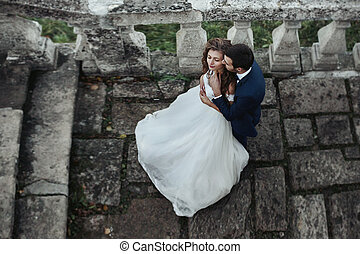 Handsome sensual groom hugging newlywed bride from behind at old castle balcony