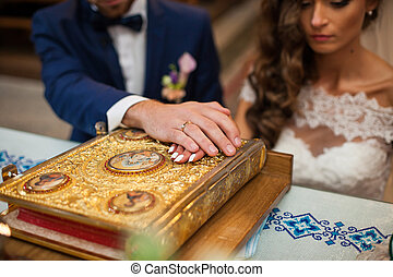 Bride and groom taking vows in church on old golden bible...