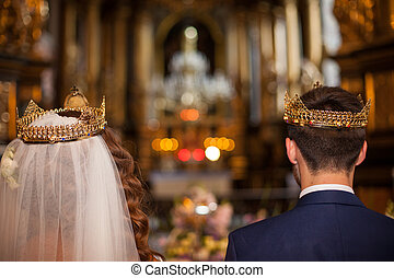 Fairytale couple, bride and groom in crowns during wedding...