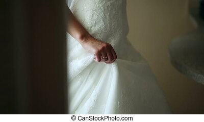 Beautiful bride in her wedding dress and veil standing at...