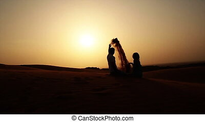 Girl and boy playing with sand in the desert