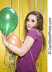 Girl with balloons and paper streamer - Young pretty girl...