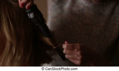Hair stylist making curls on hair using curler - Hair...