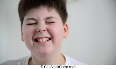 Boy teenager answers questions, grimaces and laughs - Boy...