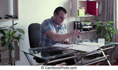 Man signs documents at the table - A man sits at a table and...