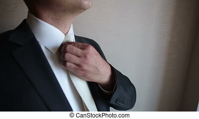 close-up of a man straightens his tie near the window
