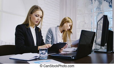 Two business woman working in the office - Two women working...