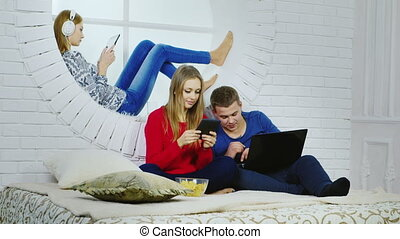 A group of young people with gadgets - relaxing at home -...