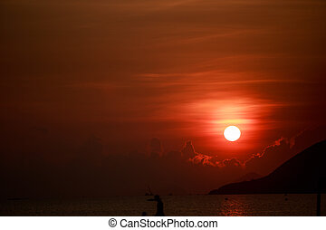 sun disk among red sky fishing boats on horizon at sunrise -...