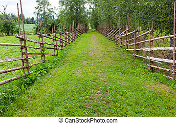 Old traditional wooden fence and road in finland
