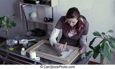 Woman apply primer on canvas - Woman with a brush on canvas...