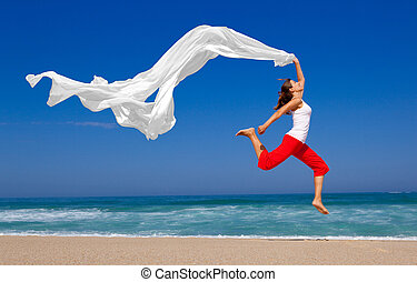 Jumping - Beautiful young woman jumping on the beach with a...