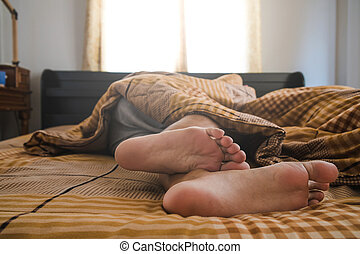 Close-up a man feet on bed in the morning