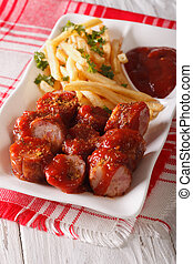 Currywurst and fries close-up on a plate. vertical -...