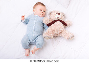 Infant boy lying in bed and grabbing teddy bear - Child with...