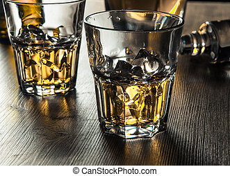 Whiskey on the rocks on a wooden table - Two glasses of...