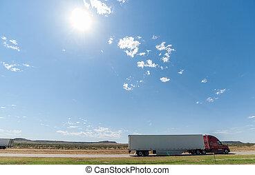 Trucks passing, mesa landforms on horizon beyond Landscape...