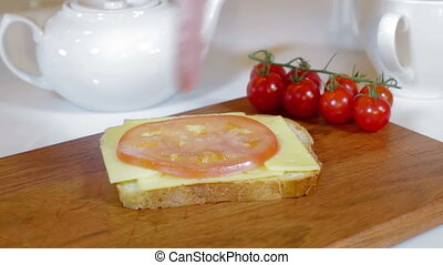 Making sandwich with tomato, ham and cheese - Man making...