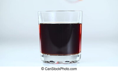 Fizzy drink is poured into a glass. White background....