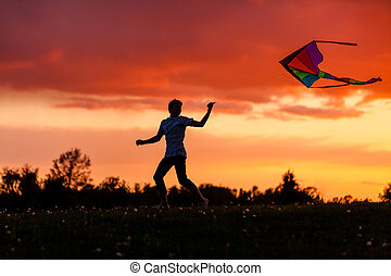 Boy flying his kite against a spectacular sunset - Boy...