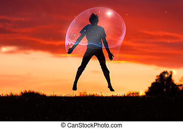Boy in a Bubble Jumping in the Air Against Sunset -...
