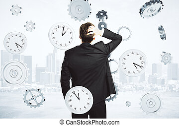 Businessman thinks about the time surrounded by clock and gears