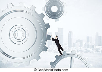 Businessman pushing gears in the mechanism