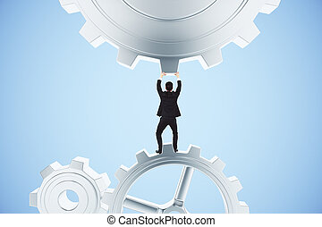 Businessman pushing gears in the mechanism on a blue...