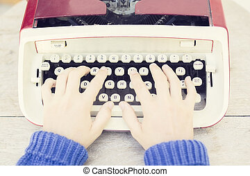 Girl with old style typewriter on the wooden table