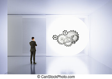 Businessman looks at the wall with painted gears in empty room