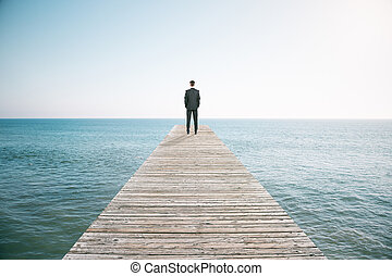 Man standing on the pier and looking into the distance of...