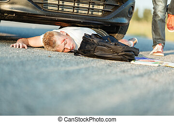 Young schoolboy knocked over by a car