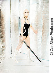 Futuristic swimwear power woman in silver room holding sword.