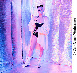 Solar futuristic blonde woman wearing fur coat and sunglasses. Standing in reflective room.