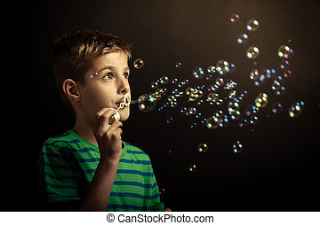 Young boy blowing soap bubbles through a hoop against a dark...